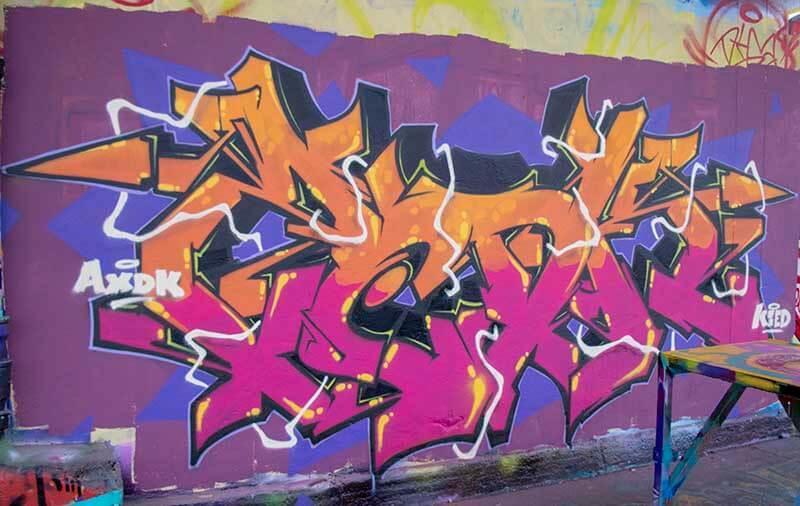 Graffiti réalisé par Kzed du crew AXDK a l'Aérosol dans le 18 eme à Paris Rose et orange sur fond violet
