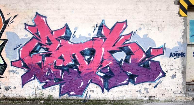 Graffiti réalisé par Kzed AXDK - couleur violet et rose contour Bleu foncé